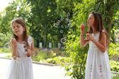 Girls blows soap bubbles — Stock Photo