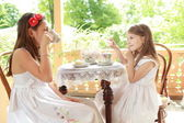 Outdoor image of beautiful little girls with tea — Zdjęcie stockowe