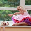 Stock Photo: Smiling young ballet dancer with pointe shoes and flowers sitting on Windowsill