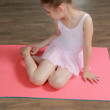 Cute young gymnast in a suit for the gym warming up on the wooden floor in the ballet hall — Stock Photo #26928003