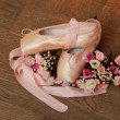 Pointe shoes with ribbons and a bouquet of flowers on a background of the old wooden floor — Stock Photo #26928523