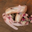 Pointe shoes with ribbons and a bouquet of flowers on a background of the old wooden floor — Stock Photo