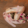 Used pointe shoes on a wooden surface — Stock Photo #26928531