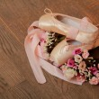 Ballet shoes with satin ribbon and a bouquet of flowers on a background of the old dark wood floor — Stock Photo #26928541