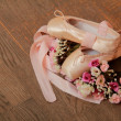 Ballet shoes with satin ribbon and a bouquet of flowers on a background of the old dark wood floor — Stock Photo