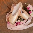 Ballet shoes with satin ribbon and a bouquet of flowers on a background of the old dark wood floor — Stock Photo #26928581