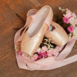 Ballet shoes with satin ribbon and bouquet of flowers on background of old dark wood floor — Stock Photo #26928581