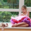 Stock Photo: Romantic dreaming young girl dressed luxuriant ball dress with frill sitting on white windowsill
