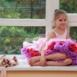 Stock Photo: Cute little girl with pointe shoes and flowers sitting on Windowsill
