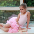 Stock Photo: Beautiful young dancer in pink leotard has been training in ballet class