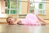 Caucasian ballerina warming up in pointe in the ballet hall on the wooden dance floor — Stock Photo