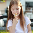 Child sits on a bench eating ice cream outdoors — Foto Stock