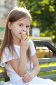 Child sits on a bench eating ice cream outdoors — 图库照片