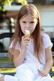 маленькая девочка в белом платье является белый мороженого на открытом воздухе — Стоковое фото