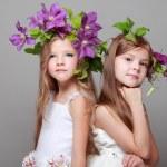 deux belles petites filles en robes blanches et des coiffures de clématites fraîches — Photo #27005263