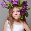 Caucasian cute little girl with beautiful hairstyle with fresh bright clematis smiles and poses for the camera — Stock Photo #27005409