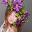 Caucasian cute little girl with beautiful hairstyle with fresh bright clematis smiles and poses for the camera — Stock Photo #27005431