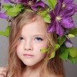 Stock Photo: Studio portrait of beautiful little girl with charming hair of purple clematis