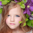 Caucasian cute little girl with beautiful hairstyle with fresh bright clematis smiles and poses for the camera — Stock Photo #27005461