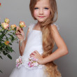 European smiling little girl in a white dress with long hair holds a healthy fresh roses with green leaves on Beauty and Fashion — Stock Photo