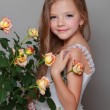 European smiling little girl in a white dress with long hair holds a healthy fresh roses with green leaves on Beauty and Fashion — Stock Photo #27005611