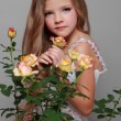 European smiling little girl in a white dress with long hair holds a healthy fresh roses with green leaves on Beauty and Fashion — Stock Photo #27005725