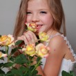European smiling little girl in a white dress with long hair holds a healthy fresh roses with green leaves on Beauty and Fashion — Stock Photo #27005797