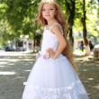 Charming young girl with long healthy hair in a beautiful white dress walking outdoors — Stock Photo