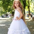 Stock Photo: Charming young girl with long healthy hair in beautiful white dress walking outdoors