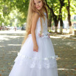 European smiling cute girl with long hair in a white wedding dress in a summer park outdoors — Stock Photo #27005901