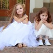 Two young girls in white wedding dresses sitting on the steps outside the building outdoors — Stock Photo