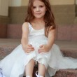Smiling cheerful little girl in a beautiful white ball gown and sneakers sitting on the stairs to the outdoors — Stock Photo #27006219