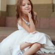 Smiling cheerful little girl in a beautiful white ball gown and sneakers sitting on the stairs to the outdoors — Stock Photo #27006283