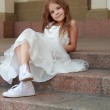 Smiling cheerful little girl in a beautiful white ball gown and sneakers sitting on the stairs to the outdoors — Stock Photo #27006307