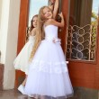Two charming little girls in long white dresses stand near the mirrored doors of the building outdoors — Stock Photo #27006427