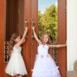 Two charming little girls in long white dresses stand near the mirrored doors of the building outdoors — Stock Photo #27006487