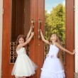 Young girl in white wedding dresses are trying to open the big doors to the building outdoors — Stock Photo