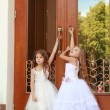 Young girl in white wedding dresses are trying to open the big doors to the building outdoors — Stock Photo #27006561