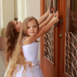 Stock Photo: Young girl in white wedding dresses are trying to open big doors to building outdoors