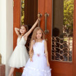 Young girl in white wedding dresses are trying to open the big doors to the building outdoors — Stock Photo #27007401