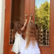 Two charming little girls in long white dresses stand near the mirrored doors of the building outdoors — Stock Photo #27007411