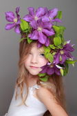 Cute little girl with beautiful hairstyle with fresh clematis — Stock Photo