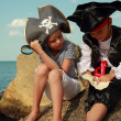Beautiful young kids pirate boy and girl holding a pirate map and a magnifying glass — Stock Photo