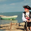 Handsome Boy dressed as a pirate on the sea coast — Stock Photo #29236693