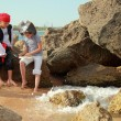 Stock Photo: Joyful little girl and boy in fancy dress pirate sitting on the shore of the sea