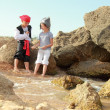 Joyful little girl and boy in fancy dress pirate sitting on the shore of the sea — Stock Photo
