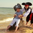 Cute little boy in a pirate costume and a little girl in a hat with a skeleton symbol — Foto de Stock