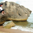 Stock Photo: Angry little boy dressed as a pirate is sitting on a large rock in the sea