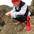Portrait of a cute young boy dressed as a pirate standing on the seashore — Stock Photo