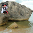Smiling young boy dressed as a pirate looking through a telescope sitting on a large rock at the seaside — Stock Photo